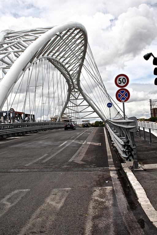 Il dischetto blu sulla destra, dopo i segnali di limite della velocità (endiadico, visto che in città la regola di base sarebbe 50 km/h) e di divieto di parcheggio sui due lati (anche questo direi superfluo, ma a Roma non si sa mai) indica l'inizio della corsia ciclabile.