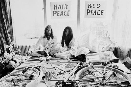 """John Lennon e Yoko Ono ad Amsterdam durante un """"bed-in"""" di protesta contro la guerra in Vietnam. Davanti a loro una bicicletta bianca, icona dei provo."""
