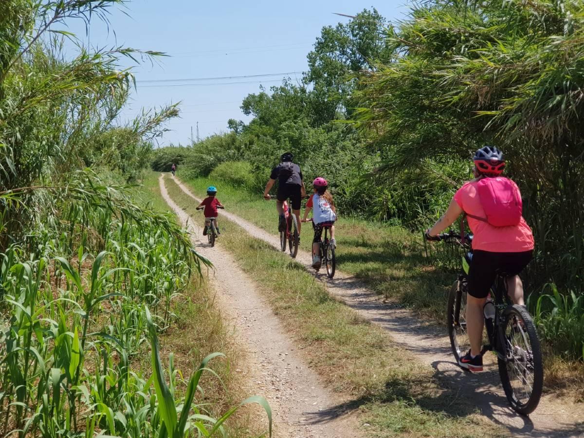 Ciclovia Tiberina Tevere - famiglia pedala su percorso sterrato lungo il fiume