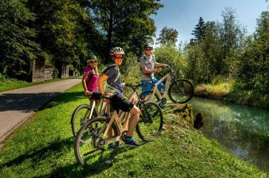 Famiglia in ebike lungo un percorso ciclabile per vacanze in bici in Italia