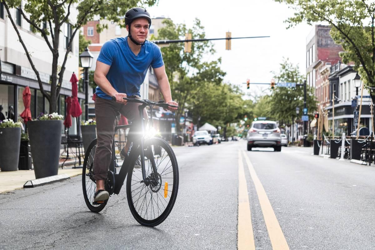 Persona che pedala un'ebike in città come mezzo alternativo all'auto